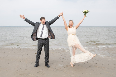 Newlyweds lifting up their hands in celebration while getting married in Denmark
