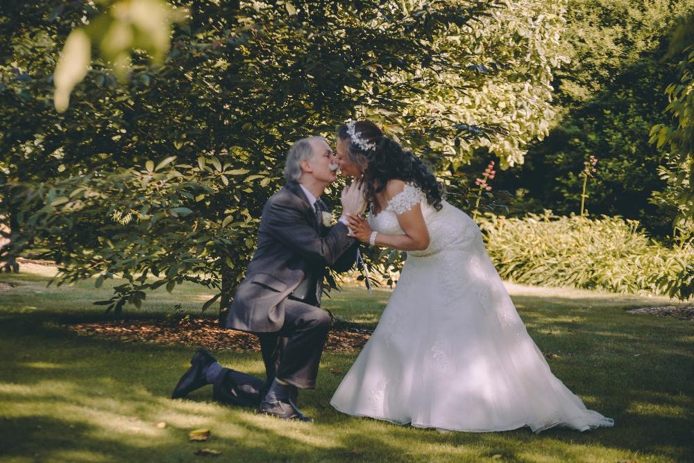 Senior groom on the knee is kissing his bride