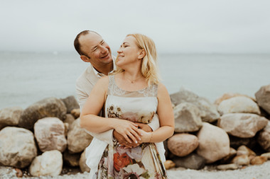 Newlyweds embracing and smiling by the seaside as they enjoy their dream elopement abroad in Denmark