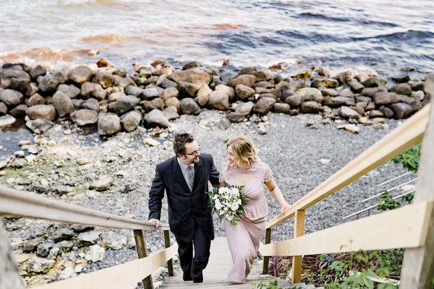 Newlyweds climbing up the wooden stairs right above the rocky coastal sealine while making the most of their wedding packages abroad for two.
