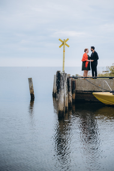 A couple by the dock enjoying their renewal of wedding vows while exploring Lolland Island.