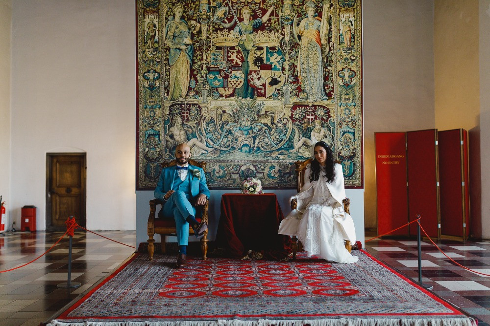 A couple posing in the historical room of Kronborg castle at their wedding in the castle
