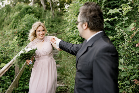 A couple dancing and smiling in the heart of green nature at Stevens Klint, pictured during their intimate wedding abroad in Denmark.