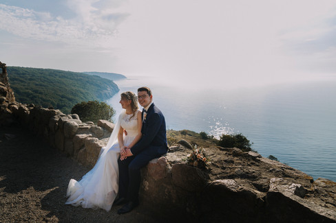 Bride and groom sitting at Hammershus Ruins enjoying their full sea view at Bornholm Island as they enjoy getting married overseas in Denmark for their adventure elopement.