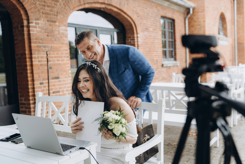 A bride and groom on a computer near a camera talking with their family watching live and following the micro wedding online