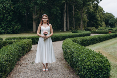 A bride posing for her portrait at the Vindeholme Castle garden during her Scandinavian wedding adventure abroad.