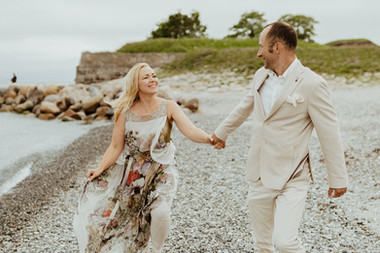 Husband and wife holding hands and walking around the beach while getting married in Denmark.