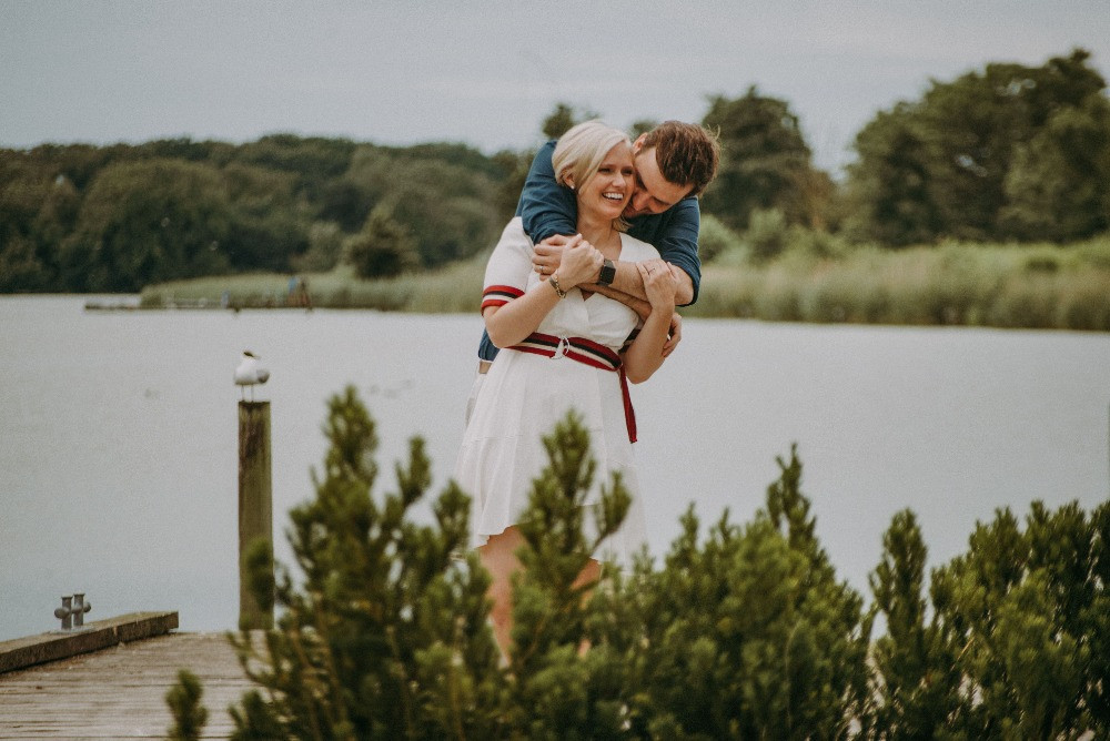 A groom hugging his bride by the Maribo lake after their elopement in Denmark