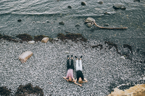An aerial shot of a same-sex couple lying by the beach at Stevens Klint during their gay marriage in Denmark.