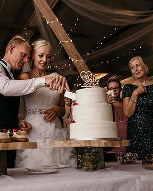 Newlyweds cutting their wedding cake at a charming Denmark wedding venue