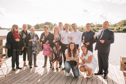 A family photo of an LGBT wedding in Denmark by the lake.