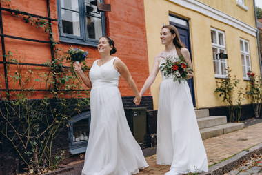 Two brides walking through Maribo and holding hands during their gay marriage in Denmark, one of the best places to elope abroad for lesbian couples.