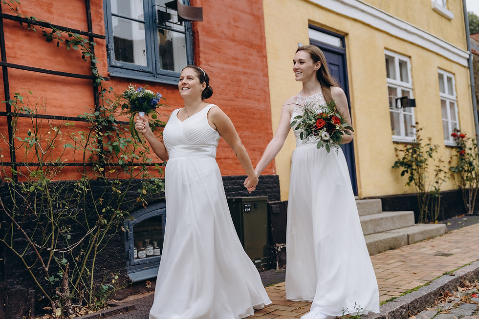 two brides holding their bouquets and walking through coloful Nordic streets during their lesbian wedding elopement in Denmark, a country where same-sex marriage is legal.