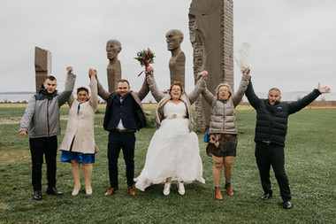A family visiting and jumping with glee at the Dodecalith in Lolland Island during their visit to Denmark for a small intimate wedding abroad.