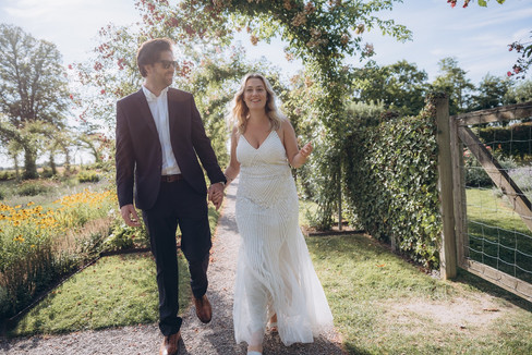 Newlyweds holding hands and walking through a romantic park at the Lolland-Falster islands in Denmark during their adventure elopement abroad.