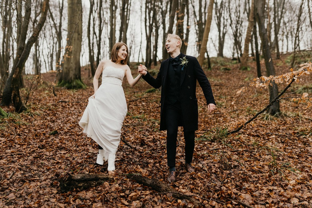 Newlyweds holding each other in hand and smiling during their walk through the forest since they got married in Denmark