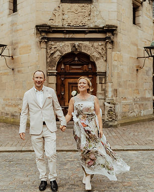 Pictured, a couple at Hamlet' Elsinore Castle holding hands, a journey that can be your for your married in Denmark after you take care of the required documents.