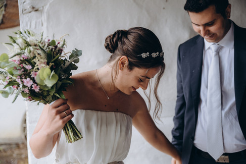 A bride looking downwards while holding her bouquet up, a candid shot of an intimate wedding abroad.