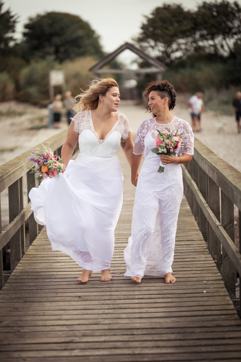 A lesbian couple walking down the pier during their beach wedding in Denmark, a perfect destination for LGBT weddings abroad in Europe.