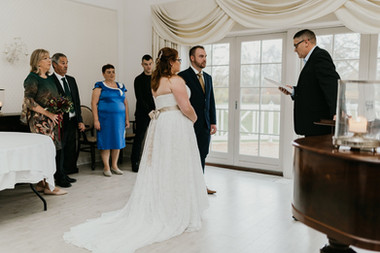 A couple during their wedding ceremony with their family as they get married in Denmark.