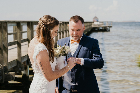 A bride putting a ring on her groom during their beach wedding in Lolland island, one of the best places to elope abroad