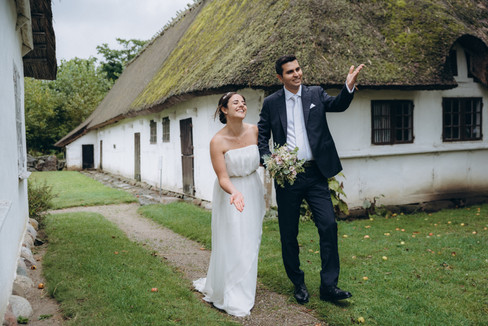 A groom holds an umbrella for his wife while they elope abroad to Denmark for a country wedding in an open-air museum, one of the best places to elope for an intimate wedding abroad.