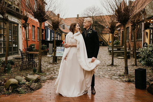 Newlyweds exploring Stege, a romantic town in Møn Island during their winter wedding in Denmark, ideal for adventure weddings that want to explore history.