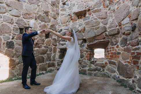 Newlyweds dancing inside the Hammershus Ruins during their adventure wedding on Bornholm Island, one of the Denmark elopement packages we offer for island weddings.