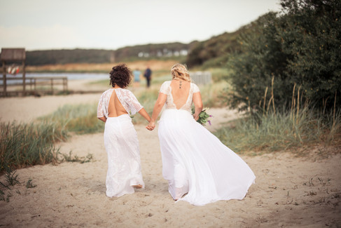 Two brides holding hands during their bohemian wedding in Denmark, a great destination for a same-sex wedding.