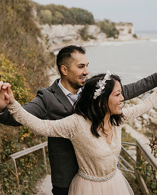 Newlyweds spreading their arms in joy as they have their elopement at Stevens Klint, one of the best places to get married in Denmark.