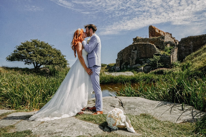 A couple kissing on the rocks as they eloped abroad to Danish island of Bornholm