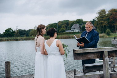 A lesbian wedding ceremony by the Maribo Lake on Lolland Island, one of the most romantic outdoor Denmark wedding venues.
