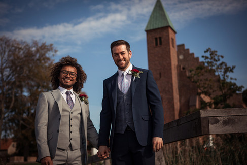 A gay couple smiling in front of the Great Cathedral after their LGBT wedding ceremony by the lake, one of the best places to get married abroad in Denmark for same-sex couples.
