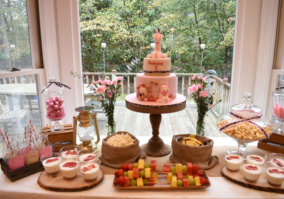 Pink safari table:  Cake Fresh fruit brochettes Graham/yogurt cups Popcorn Sweet corn Banana chips Chocolate balls Lollypops Fresh flowers bouquet