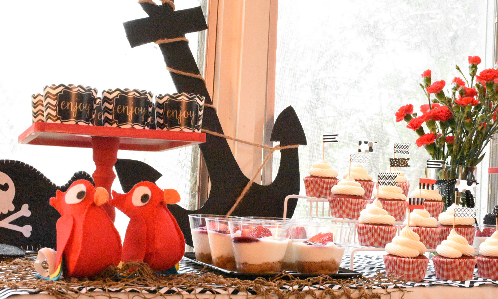 Pirates table:  Red velvet cupcakes Graham/yogurt cups Chocolate coins Felt pirates hat and parrots Fresh flowers