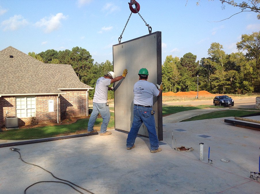 Two men placing a concrete panel of a Forever Safe Shelter on foundation slab to be welded