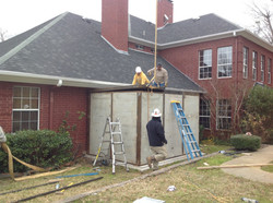 Workers placing final ceiling panel of Forever Safe Shelter attached to existing home