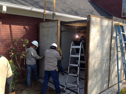 Workers welding together panels of a forever safe shelter anchored to a home