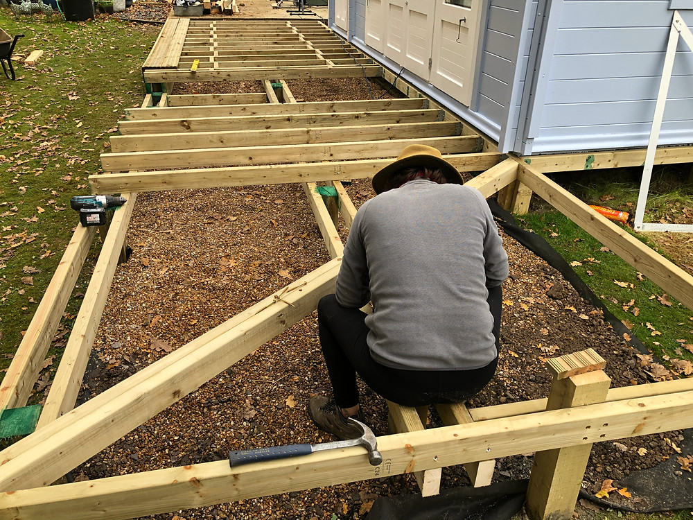 Anna is fixing the diagonal 100mm x 50mm C24 joists to the subframe
