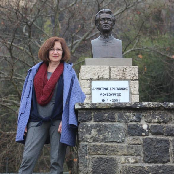 Valia Dragataki-Koronidi with her father's bronze bust in his hometown of Platanousa, Epirus. Photo supplied by the Dragatakis Archive and Valia Dragataki-Koronidi.