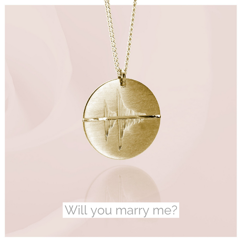 'Will you marry me' phrase engraved as a sound wave on a golden pendant.