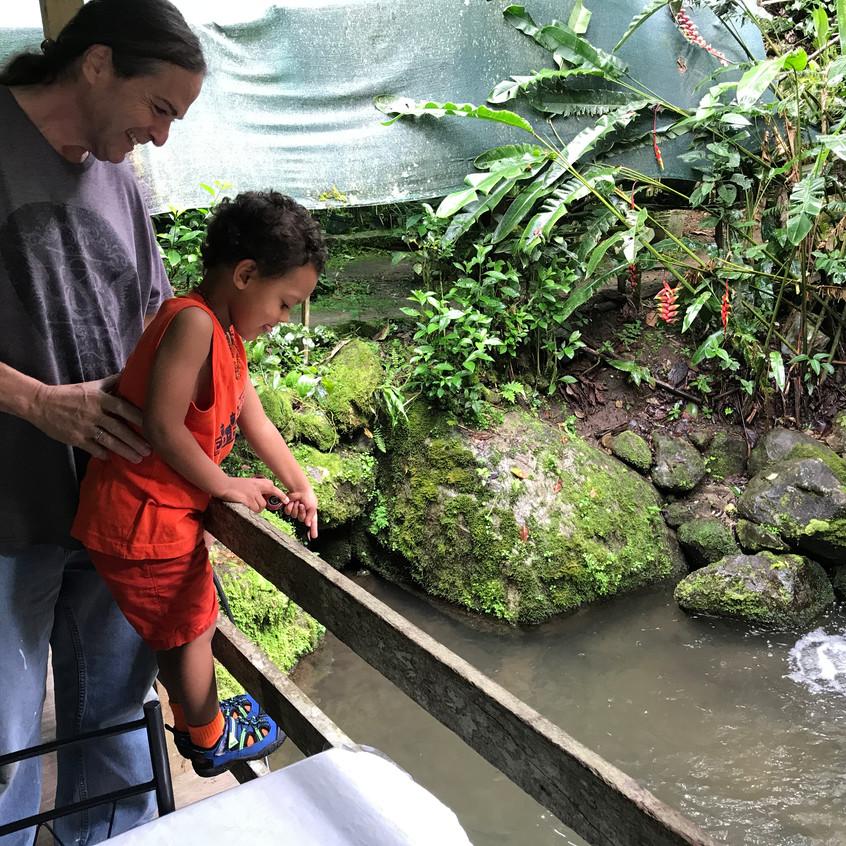 Damian feeding fish at the Truchero next door. :)