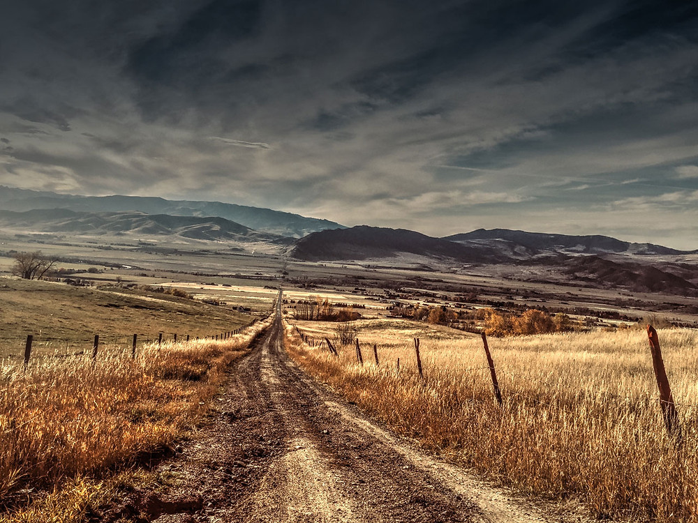 View down a dirt road that leads into a mountain valley with a dusky sky