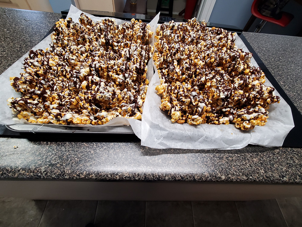 Caramel Popcorn with cashews and drizzles with both dark and white chocolate cooling down and waiting to be broken up, then  placed in containers. It takes much longer to make this than it does to eat it but it is just so addictively good.