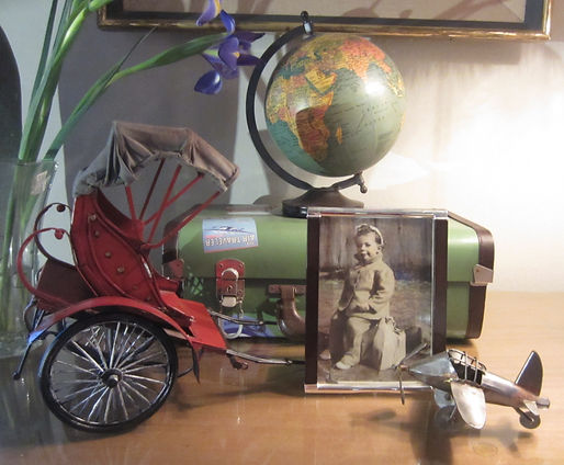 Summer travels--a globe, small suitcase, rickshaw and aeroplane, with photo of the newsletter author at age 5