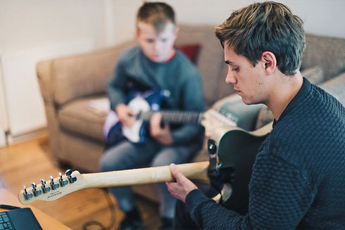 Alex-Williams-showing-young-boy-how-to-play-song-on-guitar_Alex-Williams-Music-School