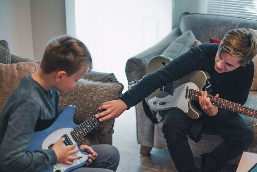 Photo-of-Alex-Williams-teaching-young-boy-electric-guitar