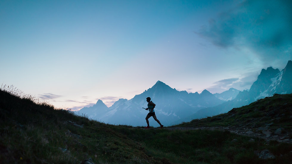 A single trail runner, silhouetted against the sky at sunrise while running in the mountai