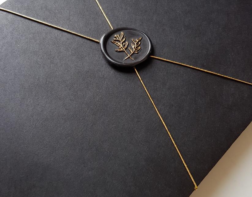 zwarte enveloppe met lakzegel