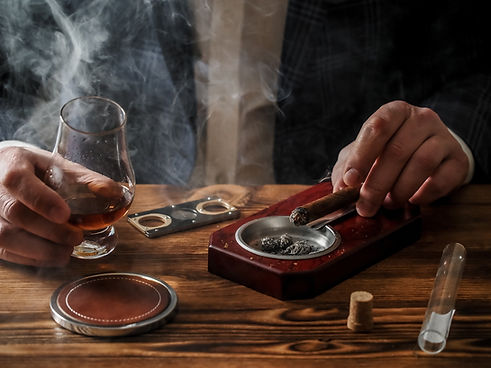 man-at-a-bar-drinks-whisky-and-smokes-a-cigar-2W4W6YT.jpg